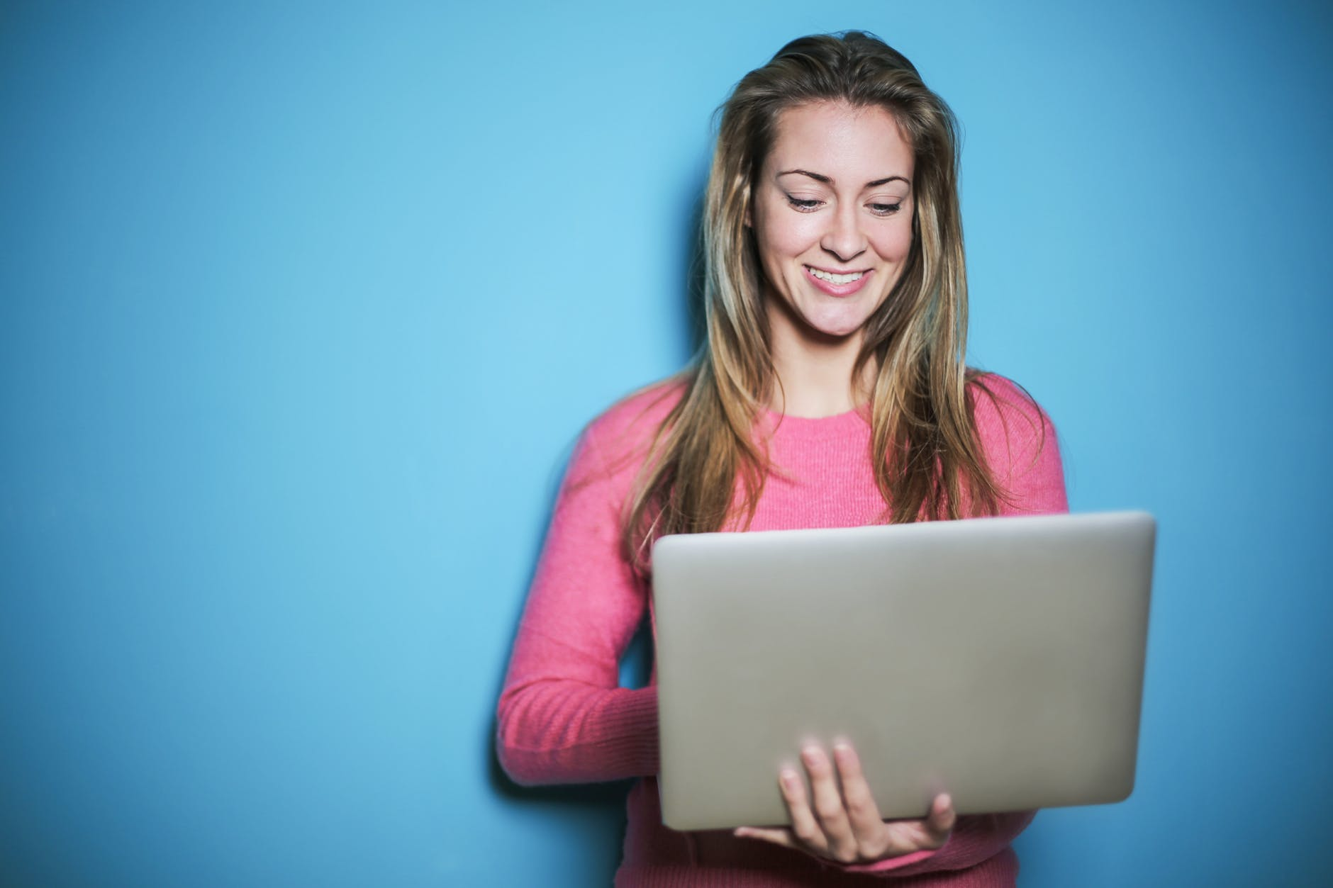 woman in pink long sleeve shirt holding silver laptop computer