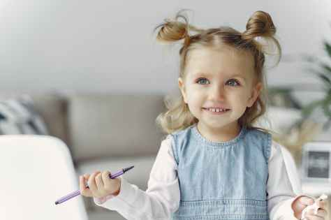 cute little girl holding purple color pen